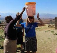 Remembering Janet: With help from a newfound friend, Emily Quint gets help balancing a bucket of water on her head.