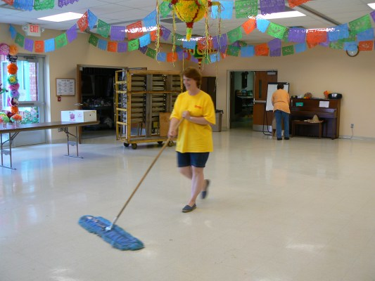 Pastor Janet Noble-Richardson sweeps the fellowship hall of her church.