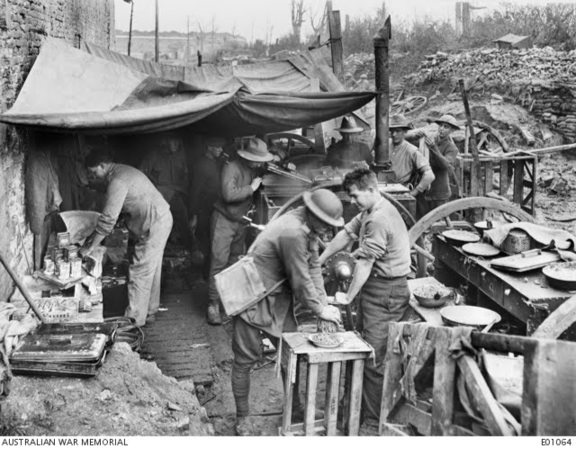 Cooks of the 2nd Battalion preparing bully beef rissoles for the evening meal at Ypres. With the aid of the mincer, the eternal 'bully' was turned into a variety of dishes.  11 November 1917. (Courtesy: Australian War Memorial)