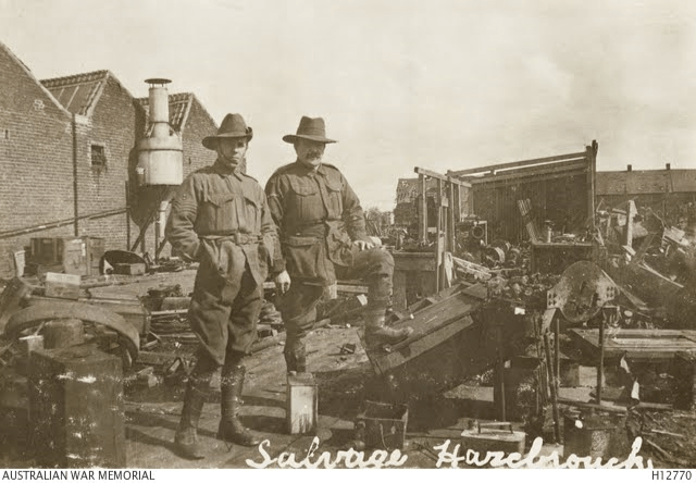 Hazebrouck, France. c. 1917. Two members of the Australian Electrical and Mechanical Mining and Boring Company, AIF, with a yard full of salvaged army items. (Courtesy: Australian War Memorial)