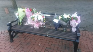 Floral tributes placed on a bench dedicated to Mary Denness.