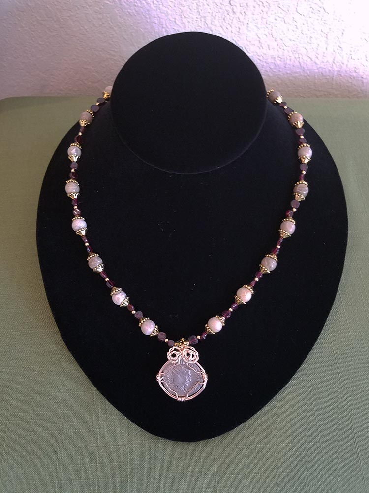 Roman As coin wrapped in gold toned copper wire with garnet and fossil coral beads