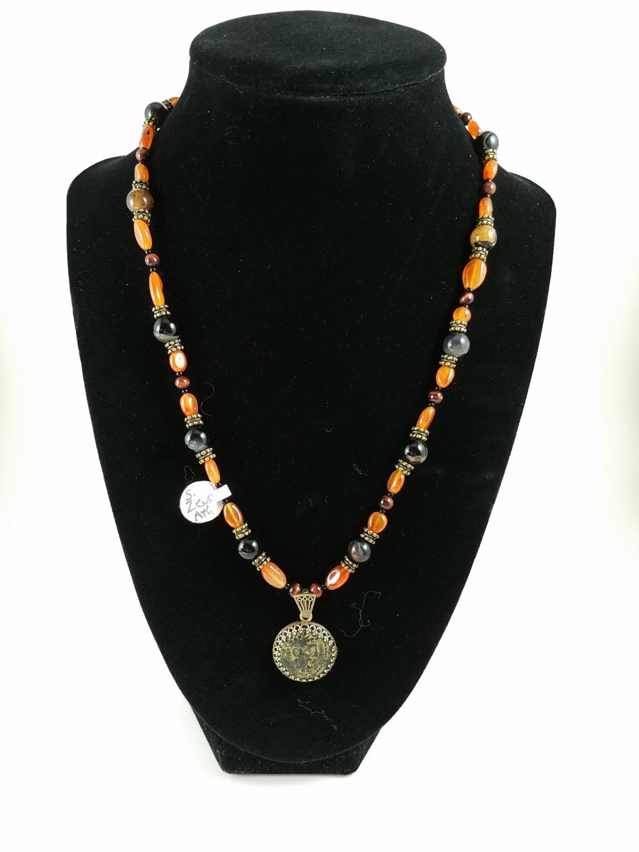Necklace featuring a coin with the Greek god Zeus decorated with black agate and orange carnelian.