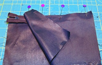 sandwich zipper between outer/liner pieces and sew with zipper foot