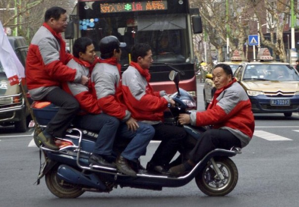 Five men sit on a electric bicycle as they cross a street in Changde
