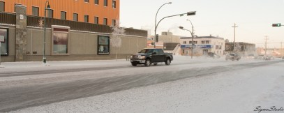 一阵寒风吹过,挂起路旁的积雪,一阵一阵连绵的雪如同飞沙一样贴着地面扫过,车辆压过的区域是路面上最滑的部分。