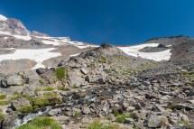 很快我们到达了 Pebble Creek,这里是即将进入山顶冰川的最后一个尚未被完全覆盖的区域;左上方冰雪覆盖之中露出的一个尖角岩石区域就是 Camp Muir 我们的终点;我们行走的路线是沿着 Pebble Creek 而上,远处冰川上稀稀拉拉的几个人所在的位置就是我们即将进入的区域
