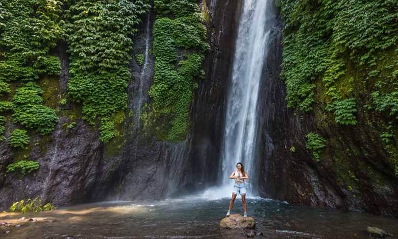 Munduk Waterfall and girl standing on rock