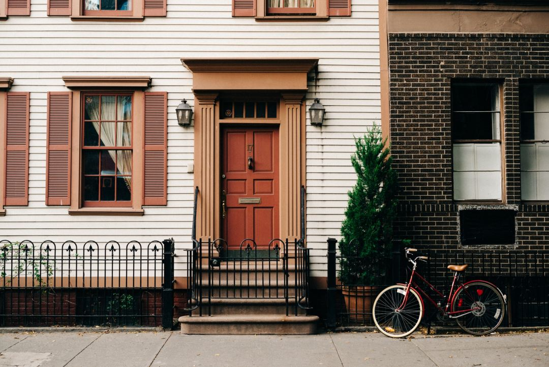 downtown townhouse with a bike in front. Photo by christian koch on Unsplash