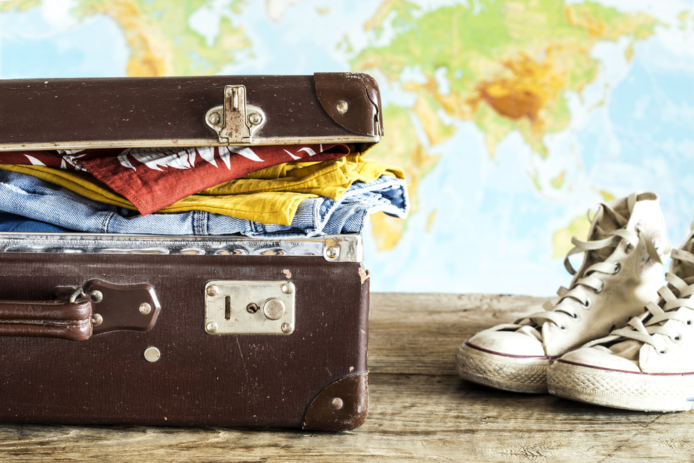 vintage suitcase packed with clothes in front of a world map