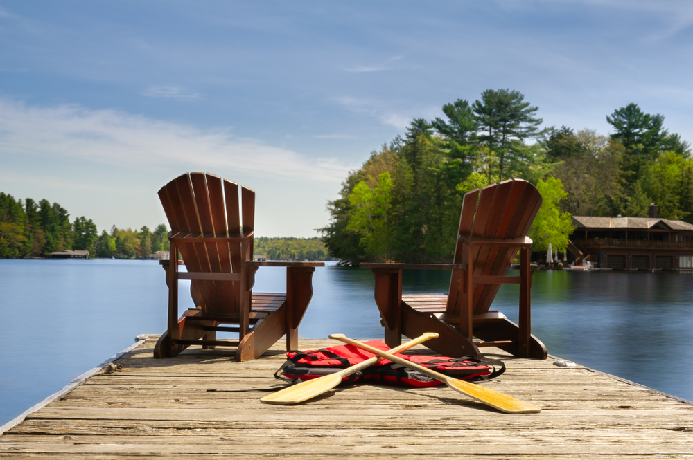 Two Adirondack chairs on a wooden dock facing the blue water of a lake in Muskoka, Ontario Canada. Canoe paddles and life jackets are on the dock. A cottage nestled between green trees is visible