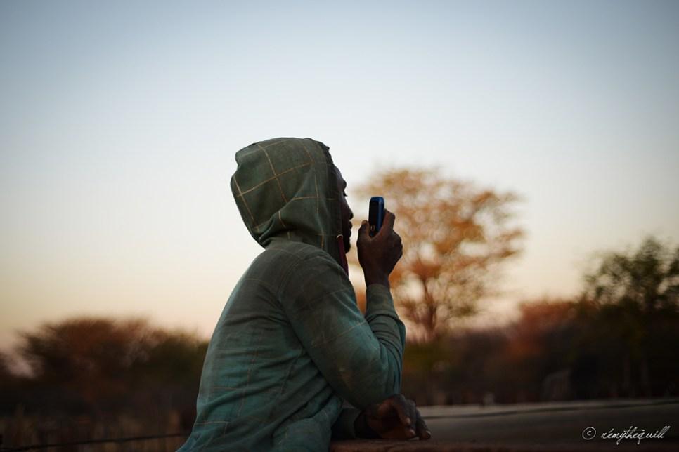 Villo, a farm worker, looks for cellular reception. Outjo, Namibia.