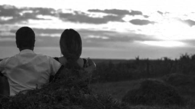 夕日を眺めるカップル 肩を抱く