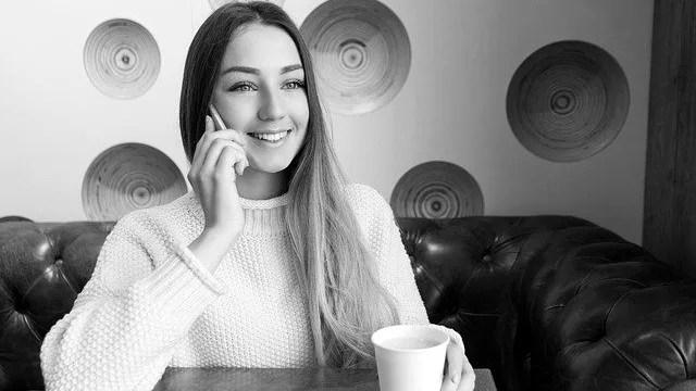 笑顔で電話をする女性 カフェ スマホ