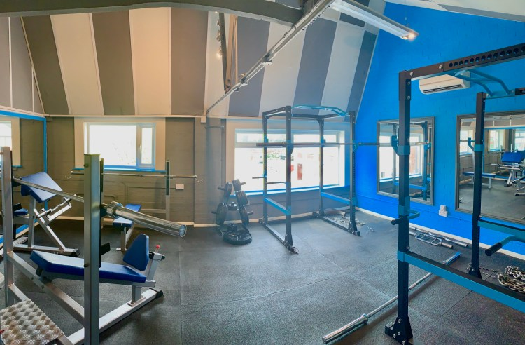 The renaissance fitness strength room has squat racks, flat and incline bench's and a preacher curl.