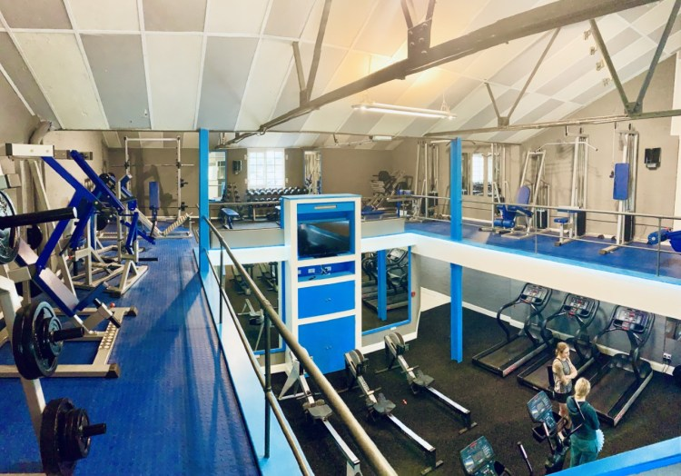 Renaissance Fitness's up stairs strength area with plate loaded strength equipment and pin loaded strength equipment.