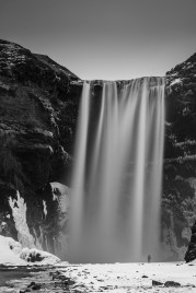 """Skogafoss. The presence of a human being gives the idea of the scale of this gigantic fall. Nikon D810, 85 mm (85.0 ƒ/1.4) 30"""" ƒ/8 ISO 200 with the big stopper and a ND 6H filter."""