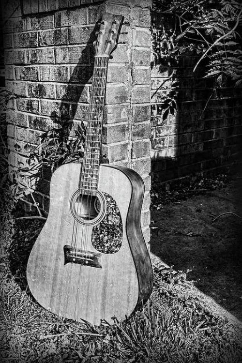 Acoustic guitar leaning against a brick wall.