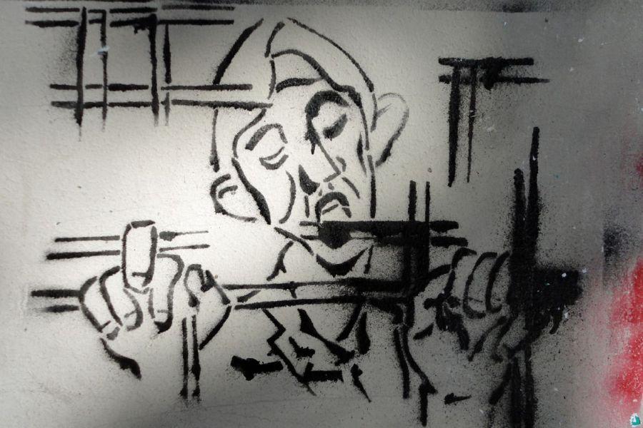 Tegning af mand bag tremmer