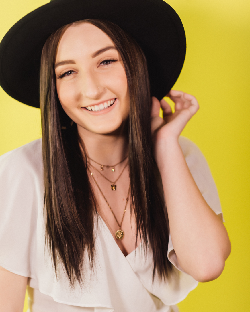 girl in black hat on yellow backdrop