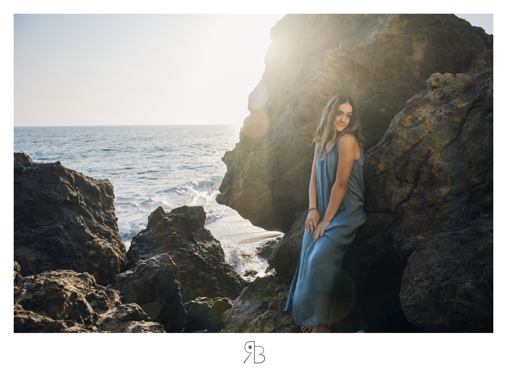 senior girl at beach leaning on a large rock structure back lit Renee Bowen Seniors