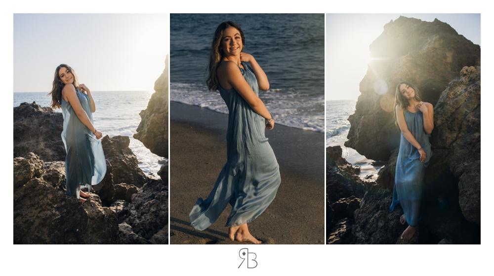 senior girl at beach wearing flowing blue long sundress near a large rock structure back lit Renee Bowen Seniors