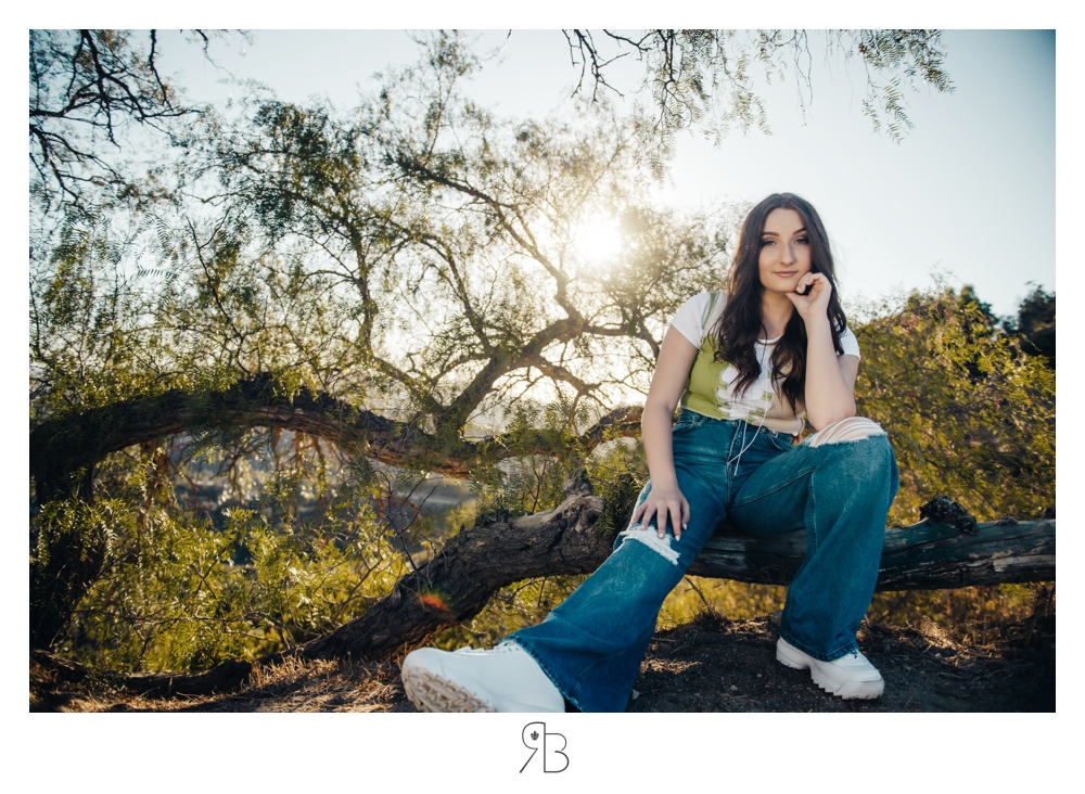 girl in jeans sitting in front of trees backlit renee bowen seniors