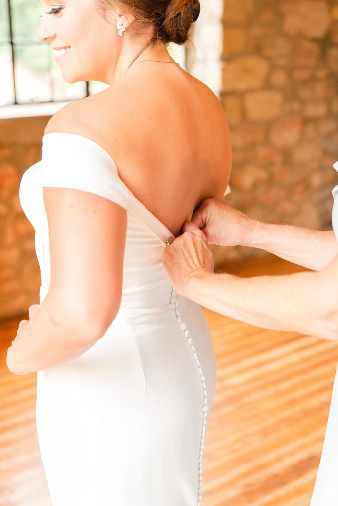 mother helps bride into wedding gown for New Hope PA wedding with Renee Nicolo Photography