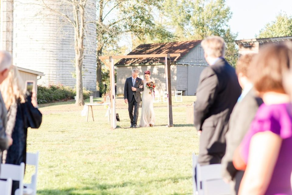 bride walks down aisle with dad photographed by Renee Nicolo Photography