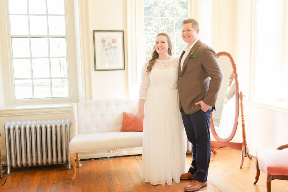 bride and groom pose during first look with family photographed by Renee Nicolo Photography