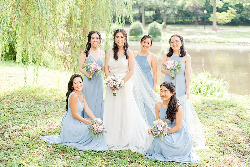 bridesmaids in blue gowns help bride with wedding dress