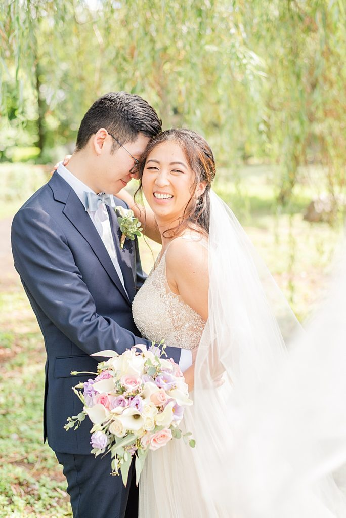 bride laughs while groom nuzzles forehead