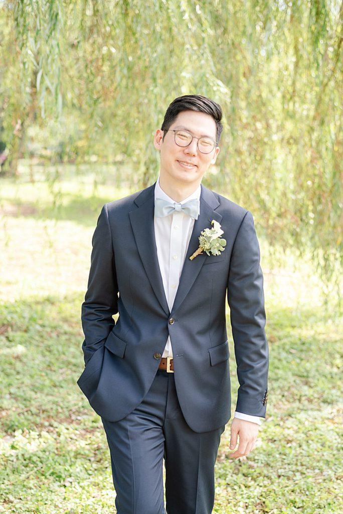 groom walks under willow tree