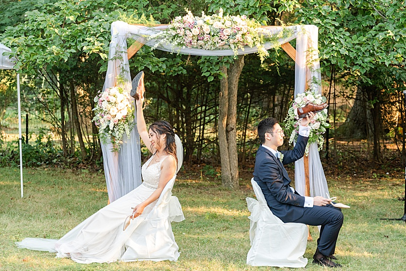 bride and groom play shoe game at backyard reception