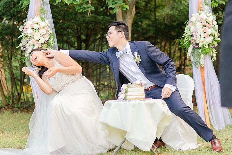 groom smashes cake in the bride's face during backyard wedding