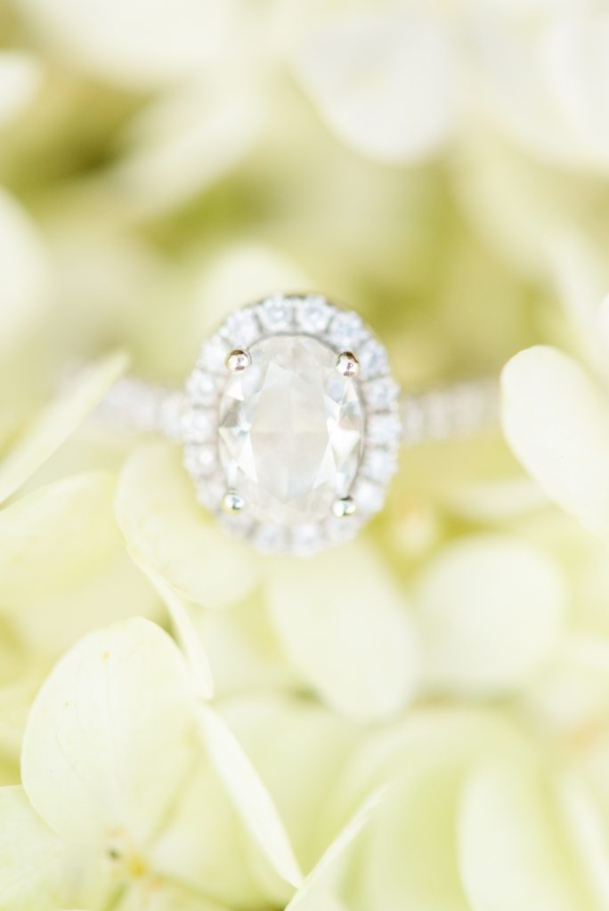 oval wedding ring rests on green flowers