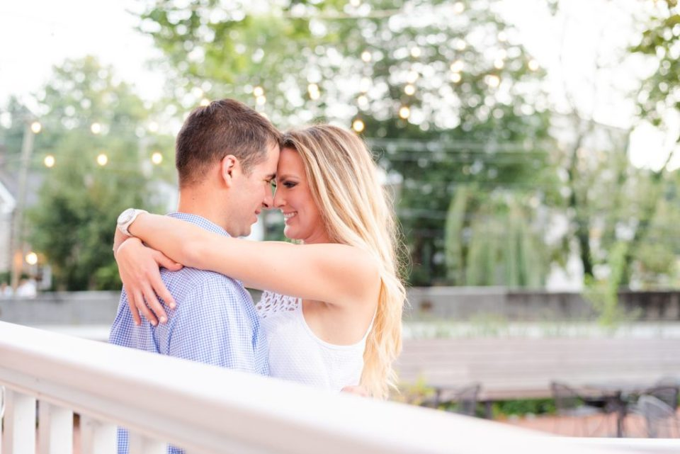 romantic engagement portrait with twinkling light in background