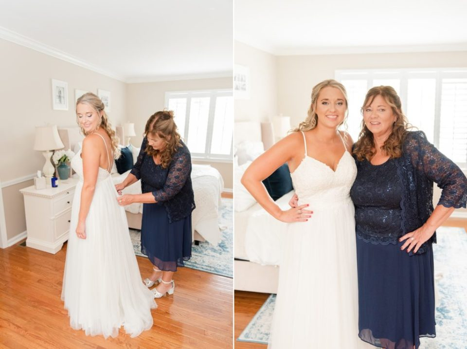 mother helps bride with wedding dress