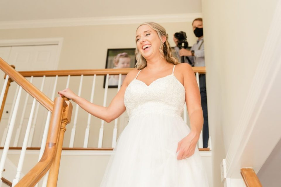 bride walks down stairs and shows bridesmaids dress