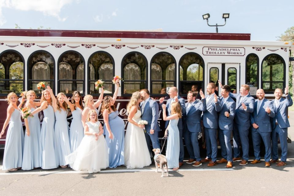 bridal party cheers while newlyweds kiss