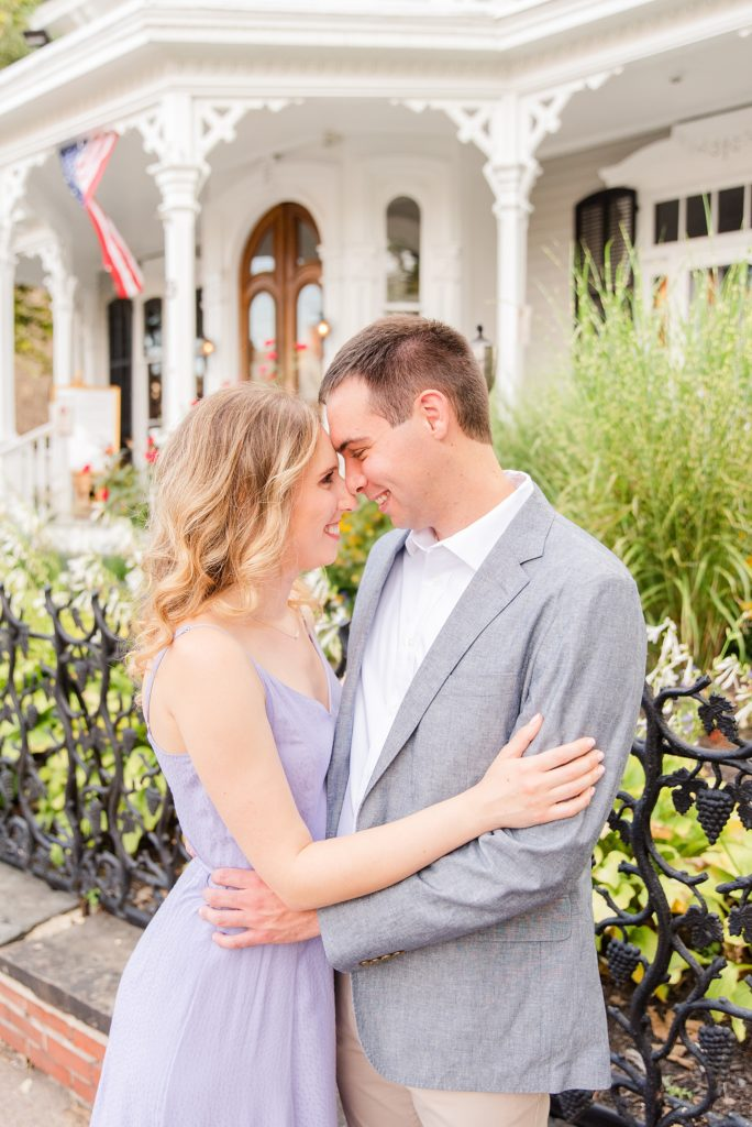 engaged couple poses in front of historical home in New Hope PA