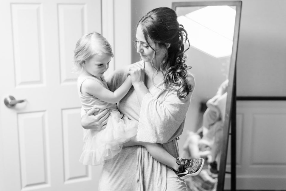 bride holds flower girl while getting ready