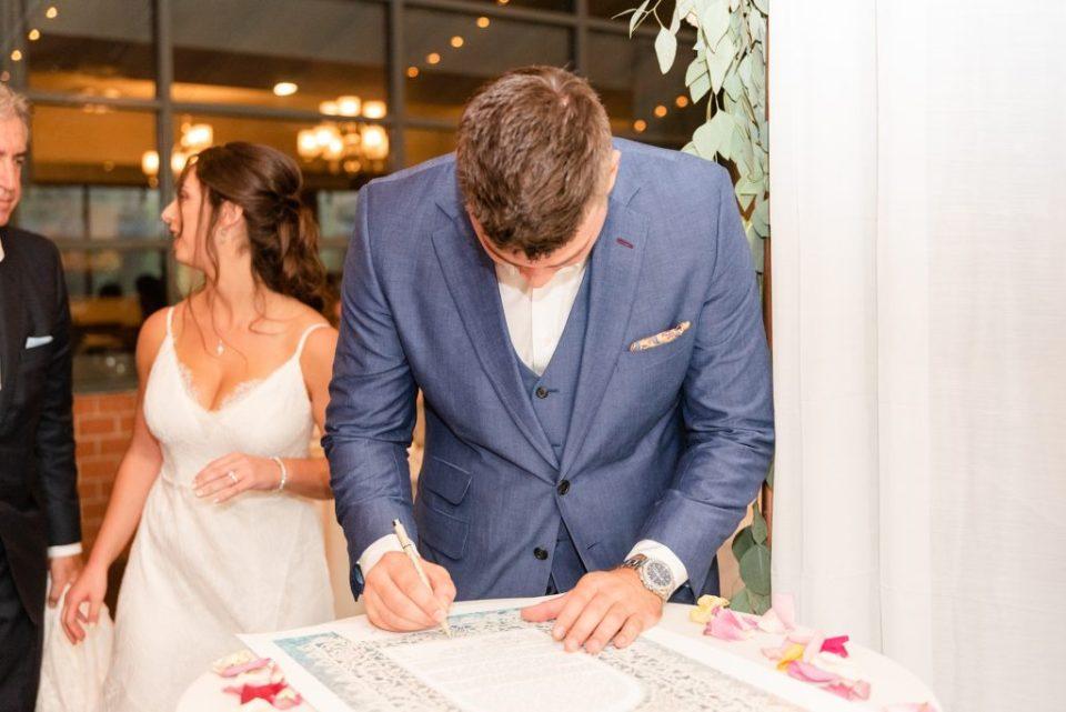 groom signs Ketubah during wedding ceremony