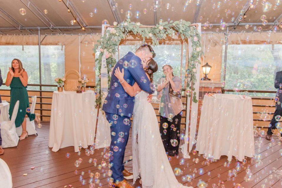 newlyweds kiss after Jewish wedding ceremony