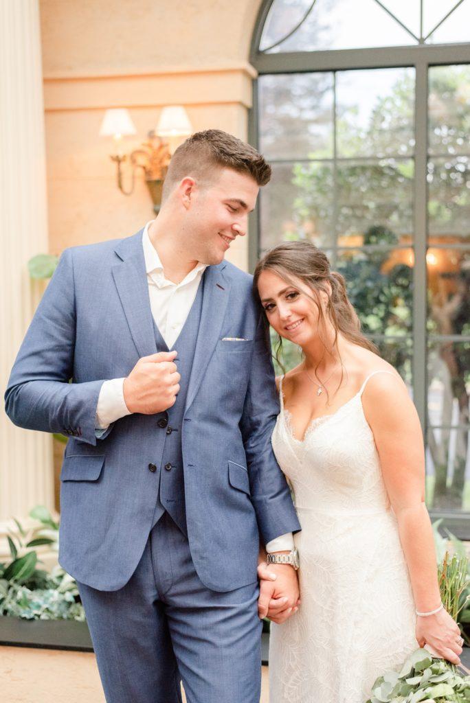 bride leans against groom's arm during wedding portraits