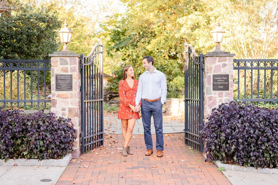 couple poses by wrought iron gate during fall New Hope engagement session