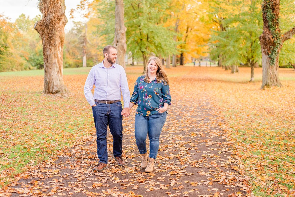 couple walks through leaves during fall engagement photos