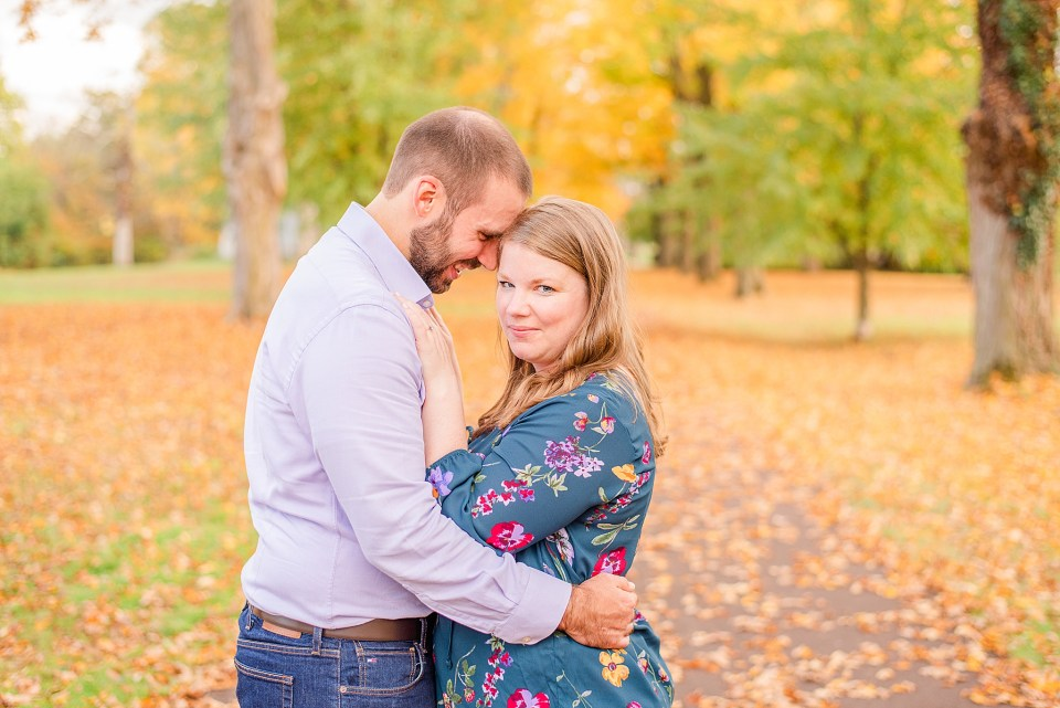 groom looks down at bride during fall engagement session