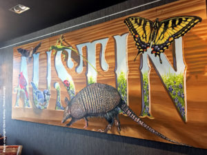 "Artwork reading ""Austin"" with an armadillo is seen at the Delta Sky Club Austin airport lounge at Austin-Bergstrom International Airport (AUS) in Austin, Texas. Photo © Chris Carley / PointsLounge"