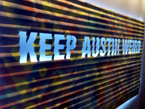"A piece of painted metal artwork with ""Keep Austin Weird"" emblazoned on it is displayed at the Delta Sky Club Austin airport lounge at Austin-Bergstrom International Airport (AUS) in Austin, Texas. Photo © Chris Carley / PointsLounge"